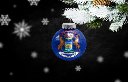 Happy new Year 2021, flag State of Michigan on a christmas toy, decorations isolated on dark background. Creative christmas concept. 免版税图像