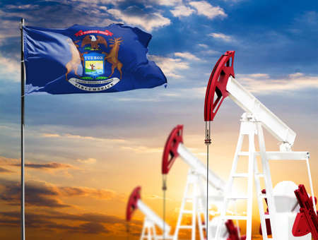 Oil rigs against the backdrop of the colorful sky and a flagpole with the flag State of Michigan. The concept of oil production, minerals, development of new deposits.