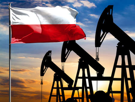 Oil rigs against the backdrop of the colorful sky and a flagpole with the flag of Poland. The concept of oil production, minerals, development of new deposits.