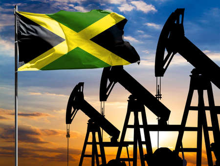 Oil rigs against the backdrop of the colorful sky and a flagpole with the flag of Jamaica. The concept of oil production, minerals, development of new deposits. 免版税图像