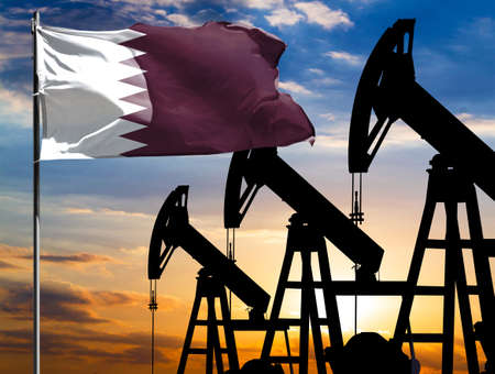 Oil rigs against the backdrop of the colorful sky and a flagpole with the flag of Qatar. The concept of oil production, minerals, development of new deposits.