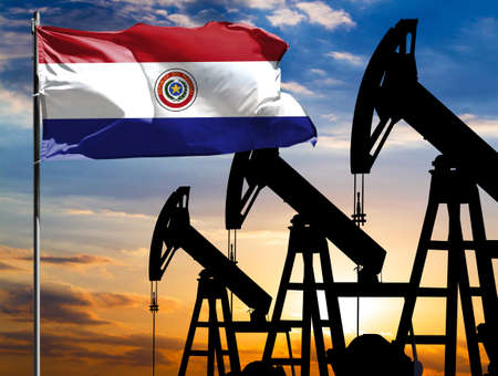 Oil rigs against the backdrop of the colorful sky and a flagpole with the flag of Paraguay. The concept of oil production, minerals, development of new deposits.