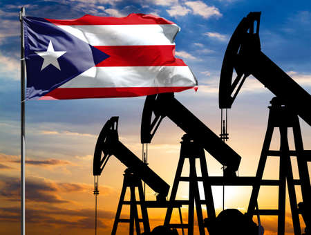Oil rigs against the backdrop of the colorful sky and a flagpole with the flag of Puerto Rico. The concept of oil production, minerals, development of new deposits.