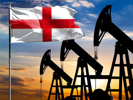Oil rigs against the backdrop of the colorful sky and a flagpole with the flag of England. The concept of oil production, minerals, development of new deposits.