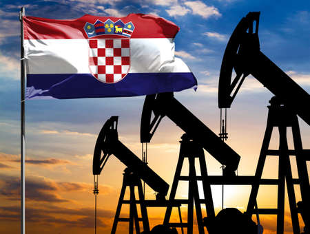 Oil rigs against the backdrop of the colorful sky and a flagpole with the flag of Croatia. The concept of oil production, minerals, development of new deposits. 免版税图像