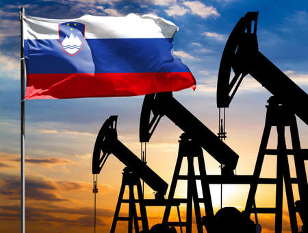 Oil rigs against the backdrop of the colorful sky and a flagpole with the flag of Slovenia. The concept of oil production, minerals, development of new deposits. 免版税图像