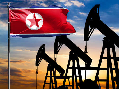 Oil rigs against the backdrop of the colorful sky and a flagpole with the flag of North Korea. The concept of oil production, minerals, development of new deposits. 免版税图像