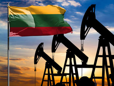 Oil rigs against the backdrop of the colorful sky and a flagpole with the flag of Lithuania. The concept of oil production, minerals, development of new deposits. 免版税图像