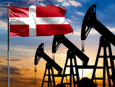 Oil rigs against the backdrop of the colorful sky and a flagpole with the flag of Denmark. The concept of oil production, minerals, development of new deposits.