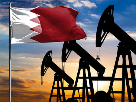 Oil rigs against the backdrop of the colorful sky and a flagpole with the flag of Bahrain. The concept of oil production, minerals, development of new deposits.