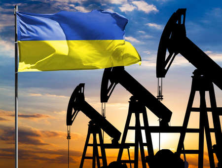 Oil rigs against the backdrop of the colorful sky and a flagpole with the flag of Ukraine. The concept of oil production, minerals, development of new deposits. 免版税图像