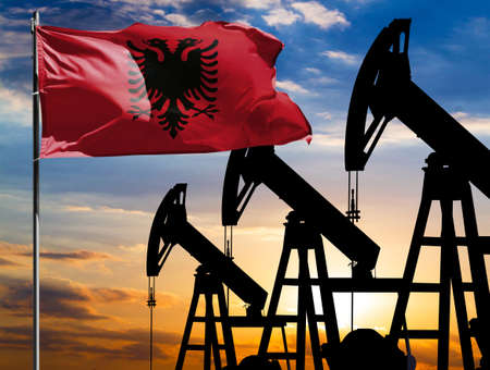 Oil rigs against the backdrop of the colorful sky and a flagpole with the flag of Albania. The concept of oil production, minerals, development of new deposits.
