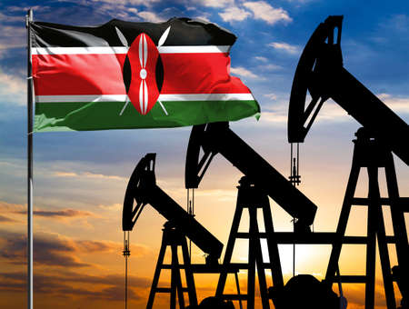 Oil rigs against the backdrop of the colorful sky and a flagpole with the flag of Kenya. The concept of oil production, minerals, development of new deposits. 免版税图像