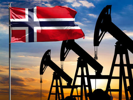 Oil rigs against the backdrop of the colorful sky and a flagpole with the flag of Norway. The concept of oil production, minerals, development of new deposits. 免版税图像