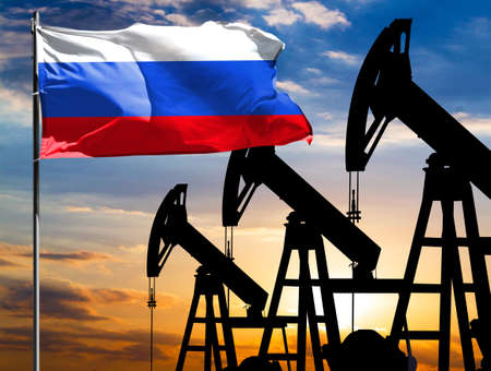 Oil rigs against the backdrop of the colorful sky and a flagpole with the flag of Russia. The concept of oil production, minerals, development of new deposits.