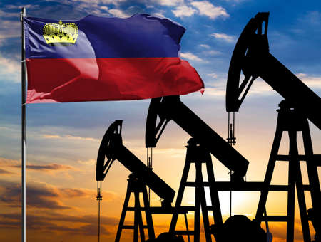 Oil rigs against the backdrop of the colorful sky and a flagpole with the flag of Liechtenstein. The concept of oil production, minerals, development of new deposits.