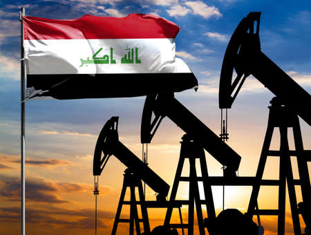 Oil rigs against the backdrop of the colorful sky and a flagpole with the flag of Iraq. The concept of oil production, minerals, development of new deposits. 免版税图像