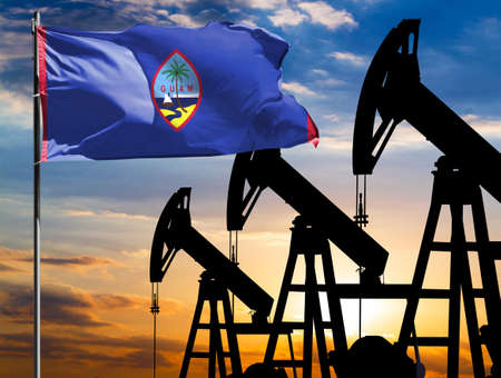 Oil rigs against the backdrop of the colorful sky and a flagpole with the flag of Guam. The concept of oil production, minerals, development of new deposits.