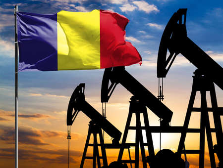 Oil rigs against the backdrop of the colorful sky and a flagpole with the flag of Romania. The concept of oil production, minerals, development of new deposits.