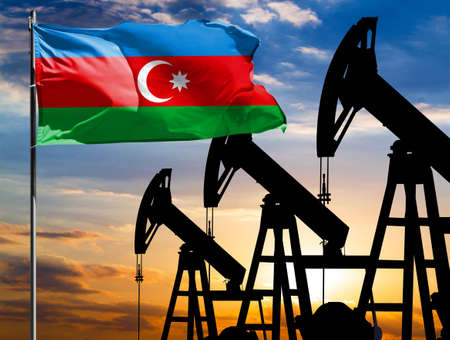 Oil rigs against the backdrop of the colorful sky and a flagpole with the flag of Azerbaijan. The concept of oil production, minerals, development of new deposits. 免版税图像