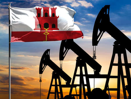 Oil rigs against the backdrop of the colorful sky and a flagpole with the flag of Gibraltar. The concept of oil production, minerals, development of new deposits.
