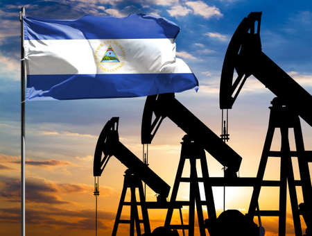 Oil rigs against the backdrop of the colorful sky and a flagpole with the flag of Nicaragua. The concept of oil production, minerals, development of new deposits.