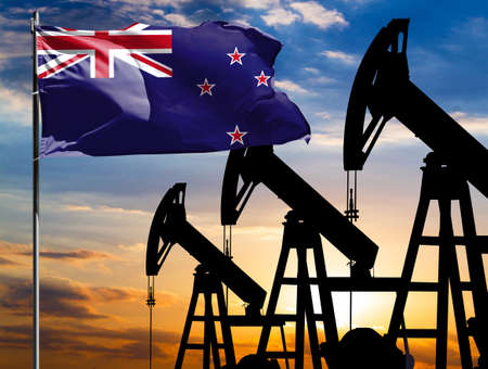 Oil rigs against the backdrop of the colorful sky and a flagpole with the flag of New Zealand. The concept of oil production, minerals, development of new deposits. 免版税图像