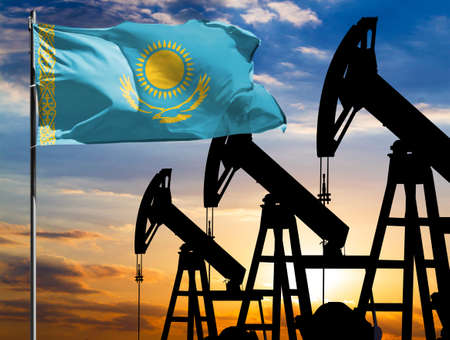 Oil rigs against the backdrop of the colorful sky and a flagpole with the flag of Kazakhstan. The concept of oil production, minerals, development of new deposits.