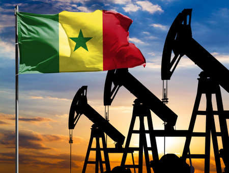 Oil rigs against the backdrop of the colorful sky and a flagpole with the flag of Senegal. The concept of oil production, minerals, development of new deposits.