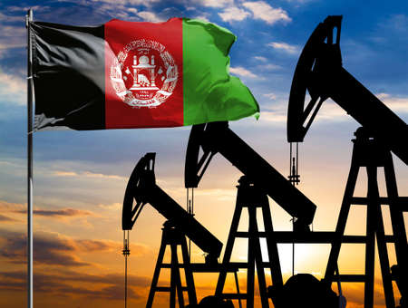 Oil rigs against the backdrop of the colorful sky and a flagpole with the flag of Afghanistan. The concept of oil production, minerals, development of new deposits. 免版税图像