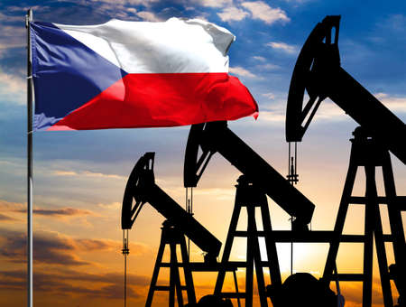Oil rigs against the backdrop of the colorful sky and a flagpole with the flag of Czech Republic. The concept of oil production, minerals, development of new deposits.