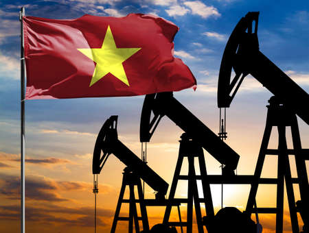 Oil rigs against the backdrop of the colorful sky and a flagpole with the flag of Vietnam. The concept of oil production, minerals, development of new deposits. 免版税图像