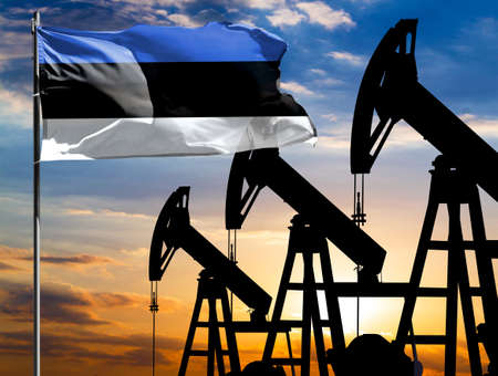 Oil rigs against the backdrop of the colorful sky and a flagpole with the flag of Estonia. The concept of oil production, minerals, development of new deposits.