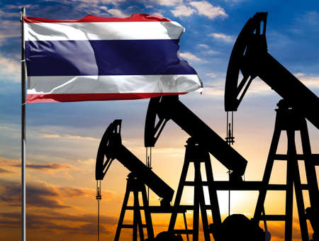 Oil rigs against the backdrop of the colorful sky and a flagpole with the flag of Thailand. The concept of oil production, minerals, development of new deposits. 免版税图像