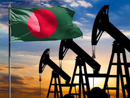 Oil rigs against the backdrop of the colorful sky and a flagpole with the flag of Bangladesh. The concept of oil production, minerals, development of new deposits.