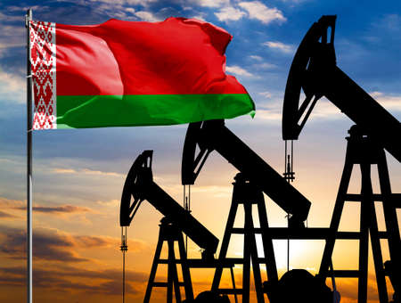 Oil rigs against the backdrop of the colorful sky and a flagpole with the flag of Belarus. The concept of oil production, minerals, development of new deposits.