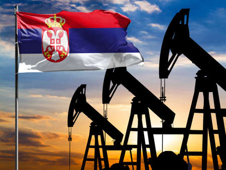Oil rigs against the backdrop of the colorful sky and a flagpole with the flag of Serbia. The concept of oil production, minerals, development of new deposits.