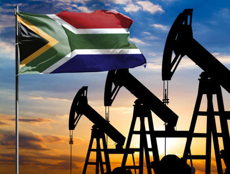 Oil rigs against the backdrop of the colorful sky and a flagpole with the flag of South Africa. The concept of oil production, minerals, development of new deposits. 免版税图像