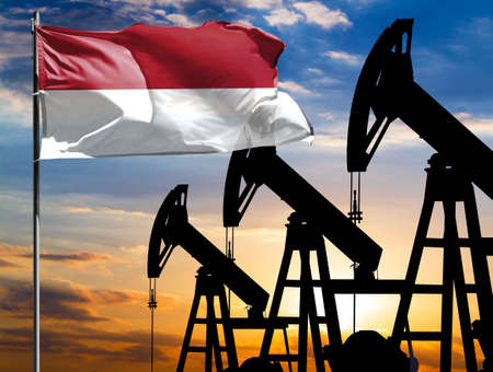 Oil rigs against the backdrop of the colorful sky and a flagpole with the flag of Indonesia. The concept of oil production, minerals, development of new deposits.