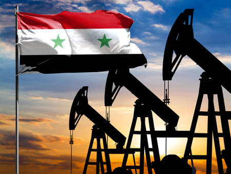 Oil rigs against the backdrop of the colorful sky and a flagpole with the flag of Syria. The concept of oil production, minerals, development of new deposits.