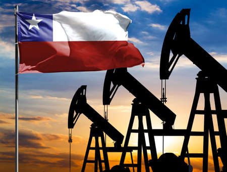 Oil rigs against the backdrop of the colorful sky and a flagpole with the flag of Chile. The concept of oil production, minerals, development of new deposits. 免版税图像