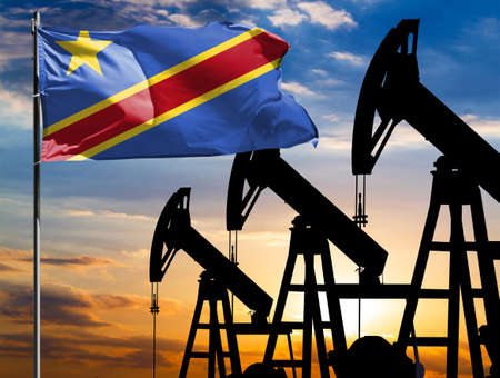 Oil rigs against the backdrop of the colorful sky and a flagpole with the flag of Congo Democratic. The concept of oil production, minerals, development of new deposits. 免版税图像