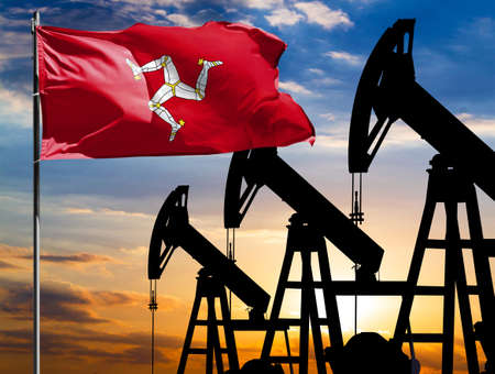 Oil rigs against the backdrop of the colorful sky and a flagpole with the flag of Isle Of Man. The concept of oil production, minerals, development of new deposits.