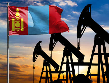 Oil rigs against the backdrop of the colorful sky and a flagpole with the flag of Mongolia. The concept of oil production, minerals, development of new deposits.