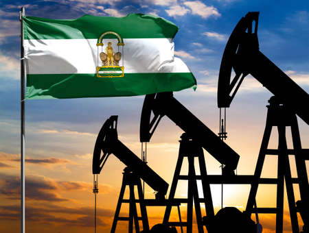 Oil rigs against the backdrop of the colorful sky and a flagpole with the flag of Andalusia. The concept of oil production, minerals, development of new deposits.