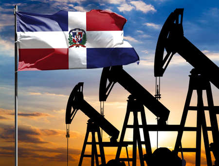 Oil rigs against the backdrop of the colorful sky and a flagpole with the flag of Dominican Republic. The concept of oil production, minerals, development of new deposits.