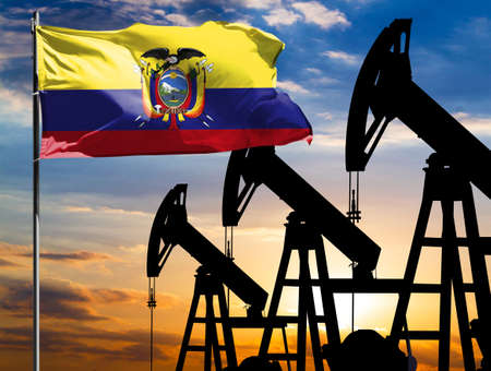 Oil rigs against the backdrop of the colorful sky and a flagpole with the flag of Ecuador. The concept of oil production, minerals, development of new deposits.
