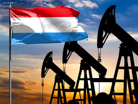 Oil rigs against the backdrop of the colorful sky and a flagpole with the flag of Luxembourg. The concept of oil production, minerals, development of new deposits.