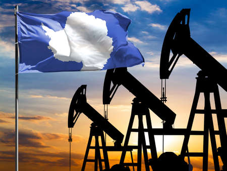 Oil rigs against the backdrop of the colorful sky and a flagpole with the flag of Antarctic. The concept of oil production, minerals, development of new deposits. 免版税图像