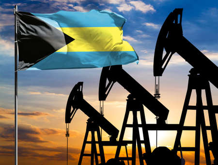 Oil rigs against the backdrop of the colorful sky and a flagpole with the flag of Bahamas. The concept of oil production, minerals, development of new deposits.